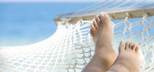 Woman's feet in a hammock with ocean in background. Close up