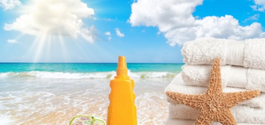 Sunscreen lotion with towels and flip flops overlooking the ocean